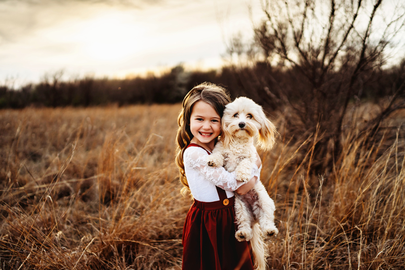 family photographer, little girl holds her little white dog outdoors in a grassy field