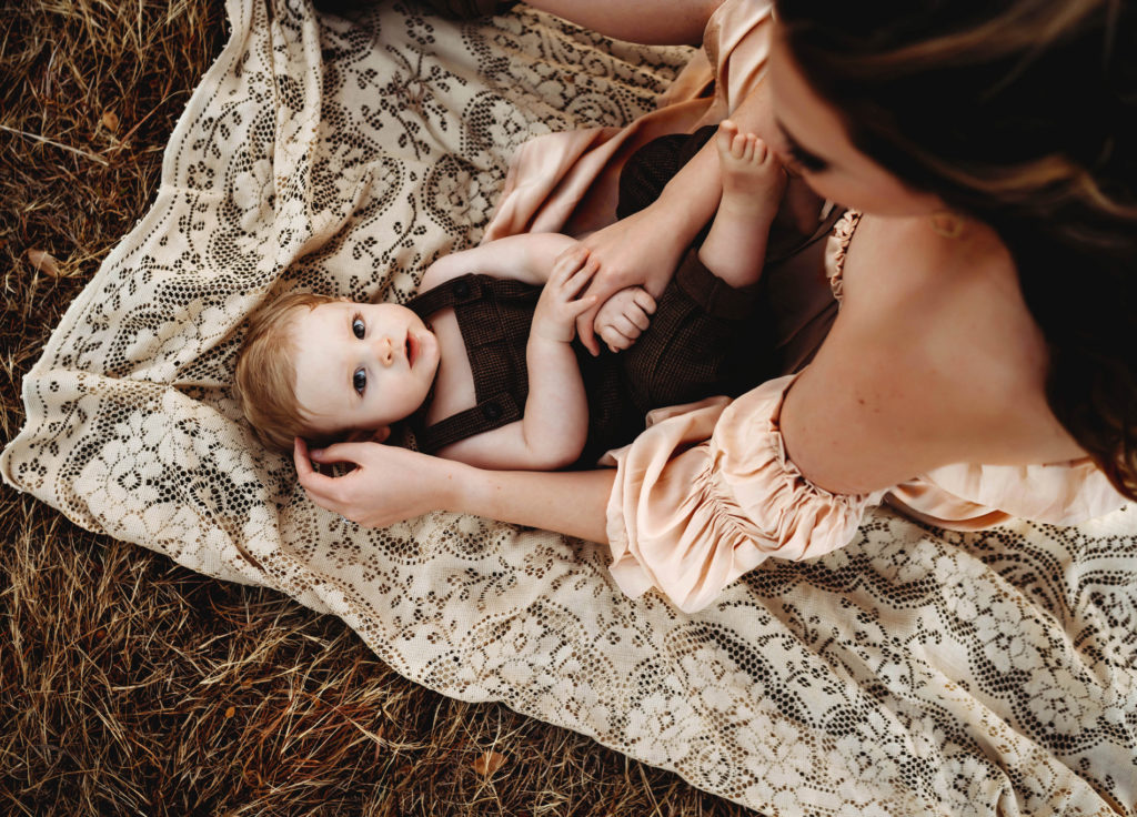 family photographer, mother looks down at baby laying on a floral patterned blanket in the grass