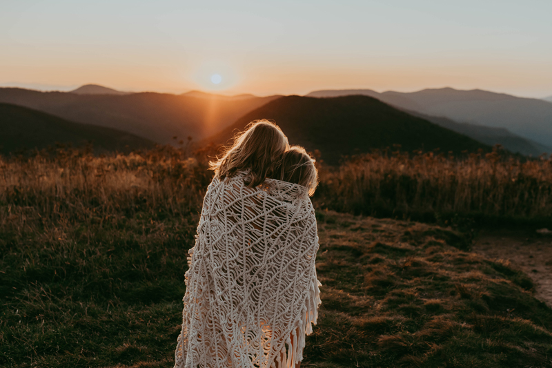 family photography, two sisters huddle together in crochet throw blanket outdoors in a grassy field at sunset