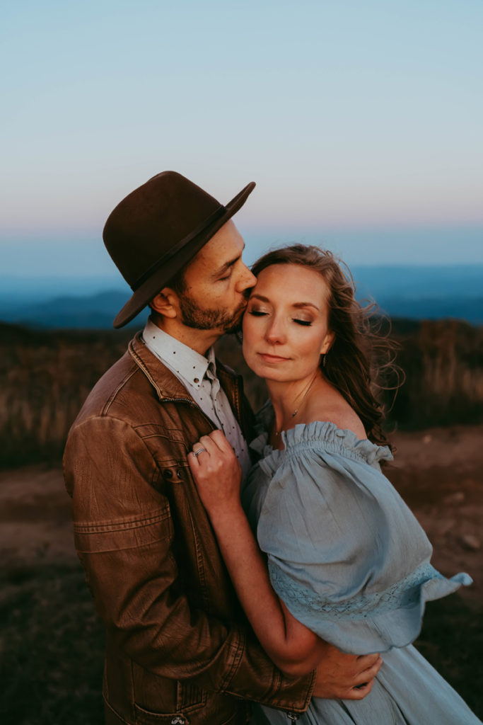 family photographer, man in jacket and hat kisses woman in blue dress