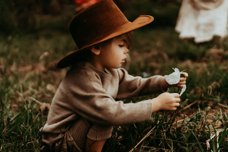 family photography, toddler with cowboy hat examines flower in the grass