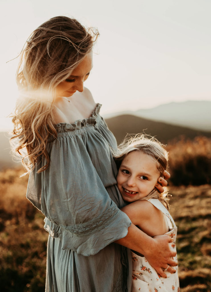family photographer, young smily daughter hugs mother outdoors in a field