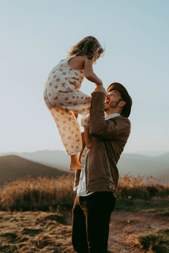 family photography, young daughter climbs up on dad as he holds her hands in the outdoors