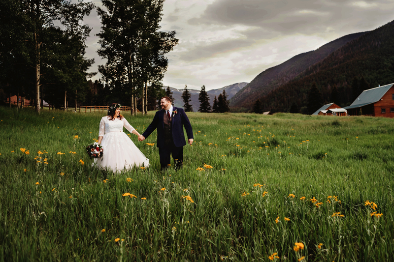 Family Photography, newly wed couple walk through flowery meadow, barn in the distance